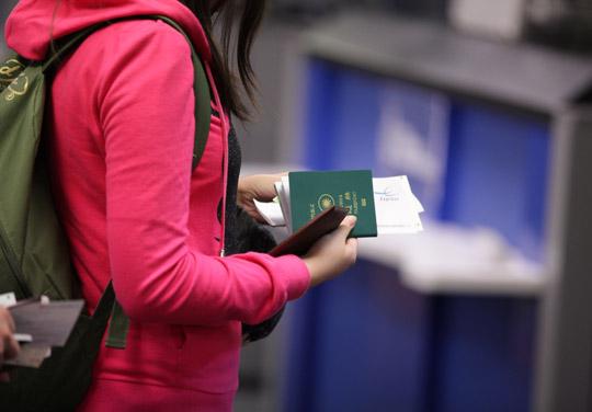 Dívka drží v ruce cestovní pas