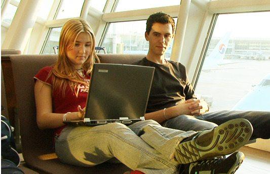 Dva mladí lidé sedí s notebookem na letišti