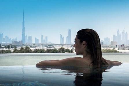 žena v bazénu s výhledem na město